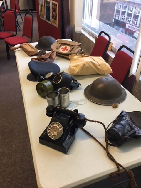 Display of wartime memorabilia on table - telephone, gas masks, helmets and bags