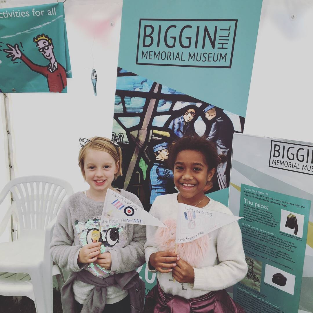 Two children holding flags in front of Biggin Hill Memorial Museum posters