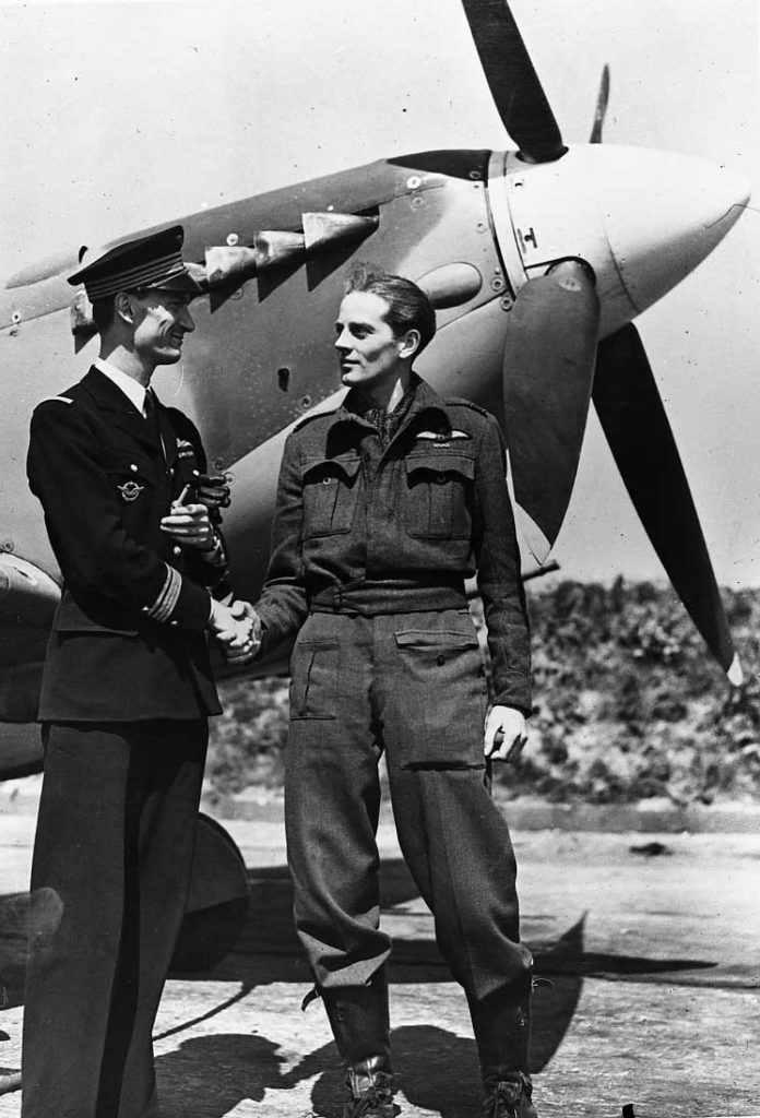 Two men - one in officer's uniform, shaking hands in front of an aircraft