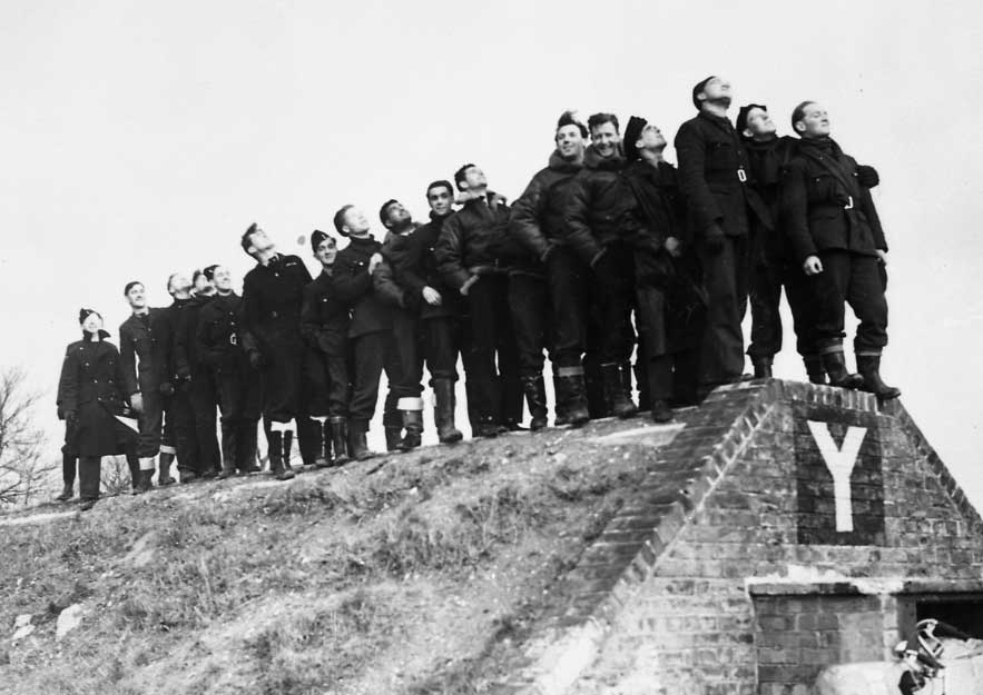 Lots of men in a crowd standing on top of a shelter