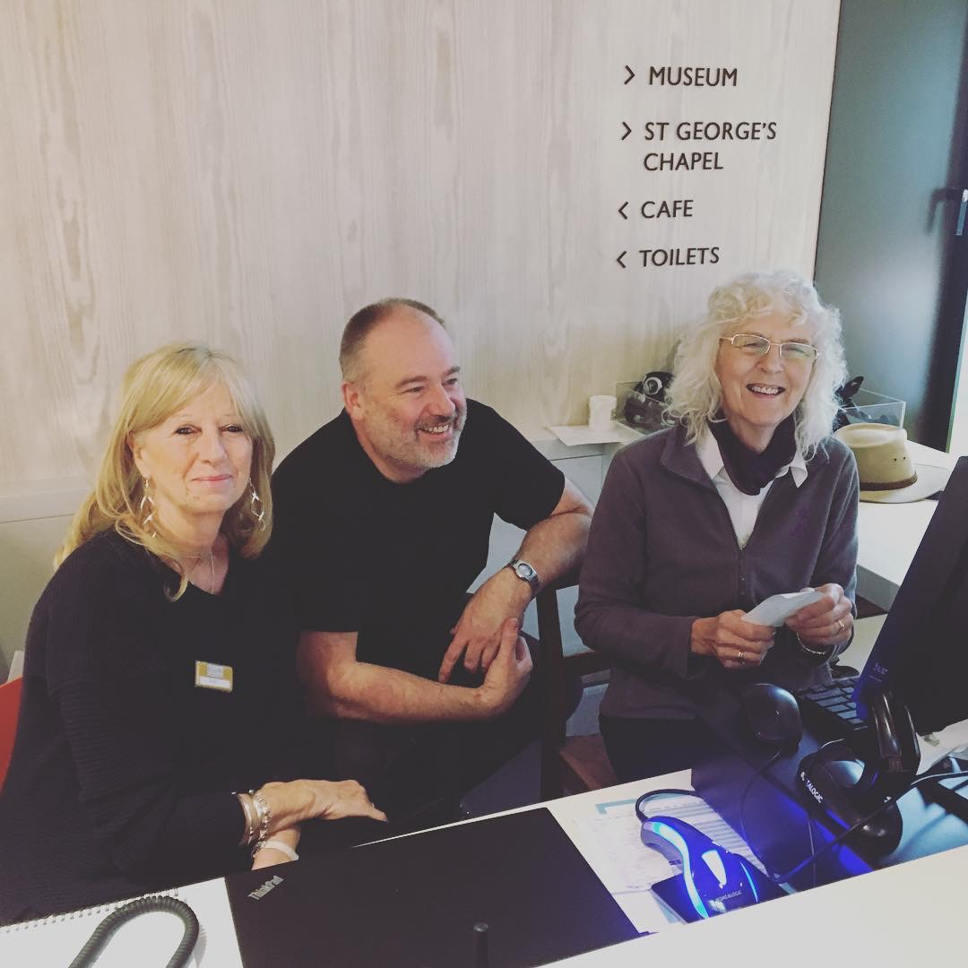 Three people smiling at reception desk